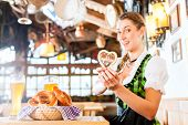 Bavarian woman wearing dirndl got gingerbread heart in german beer restaurant