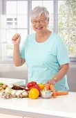 Elderly lady preparing healthy food in kitchen, using vegetables and brown bread.