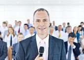Busines man standing in front other business person and holding microphone