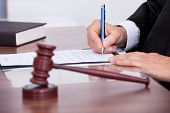 stock photo of courtroom  - Male Judge Writing On Paper In Courtroom - JPG