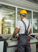 foto of heavy equipment operator  - Operator wearing safety hat in a factory control room - JPG