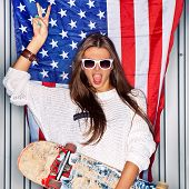 pic of skateboarding  - Beautiful girl with a skateboard in front of a flag of the U - JPG