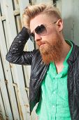 close up portrait of a young casual redhead bearded man with his hand in his hair, looking away from