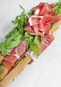 Grissini with prosciutto crudo and vegetables on white
