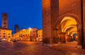 Arched passage and medieval towers on cobbled town square early in the morning in Alba, Italy.