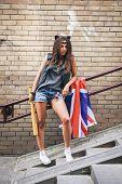 Bad Girl Holding A Baseball Bat And British Flag At Street.