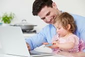 Father With Child Using Laptop At Home