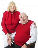 A happy senior couple in red sweaters.  On a white background.