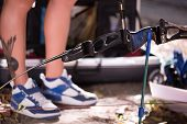 foto of longbow  - Selective focus on the great bow lying on the ground near the legs wearing nice sneakers on background - JPG