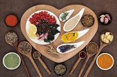 stock photo of immune  - Superfood immune boosting selection in white porcelain dishes and wooden bowls over heart shaped board and lokta paper background - JPG