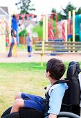 Disabled Little Boy In Wheelchair Watching Children Play On Playground