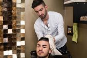 Hairdresser Washing Man Head In Barber Shop