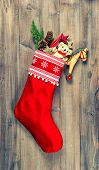 stock photo of nostalgic  - christmas stocking with nostalgic vintage toys decoration and pine branch over wooden background - JPG