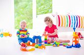 picture of car-window  - Two happy children playing with toy cars cute curly toddler girl and a funny baby boy brosther and sister sitting on the floor building blocks in a sunny white bedroom with big window - JPG