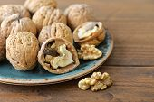 picture of walnut  - Walnut kernels and whole walnuts on plate on rustic old wooden background - JPG