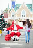 Full length of Santa Claus about to embrace girl in courtyard