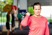 Portrait of fit young woman lifting kettlebell at gym