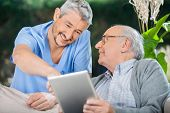 Smiling male nurse assisting senior man in using tablet PC at nursing home porch