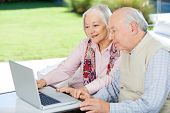 Senior couple using laptop while sitting at nursing home porch