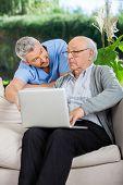 Male nurse assisting senior man in using laptop at nursing home porch