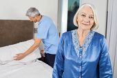 Portrait of smiling senior woman with caretaker making her bed in background at nursing home