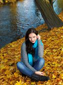 Pretty Woman in Autumn Outfit Sitting on Dry Leaves Along the Riverside. Looking on Right Side Frame while Hand on Face.