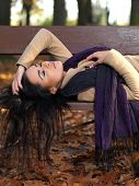 Long Hair Young Woman Sleeping on Brown Bench in Autumn Outfit. Captured in Half Body Portrait.