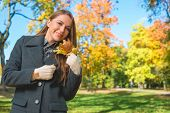 Smiling Young Blond Woman in Gray Coat Holding Dry Leaves. Captured Outdoor with Nature Background.