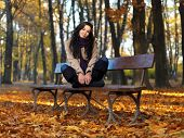 Long Woman in Autumn Fashion Outfit Sitting on Bench. Isolated on Nature Background.