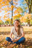 Pretty Young Woman Sitting on Grassy Ground with Dried Leaves  Listening Music on Ipod with Headset.