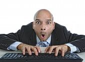 stock photo of addict  - young businessman typing on computer keyboard with funny face expression on watching porn online and internet chat and social network addiction concept isolated on white background - JPG