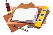 Notebook and measuring instruments on textured paper.
