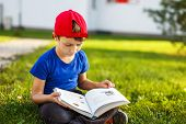 foto of fable  - Little boy reading fable book outdoor portrait - JPG