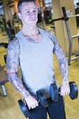 Man Making Front Raises - Workout Routine .