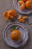 stock photo of mandarin orange  - vintage pewter plates with mandarin oranges and orange segments - JPG