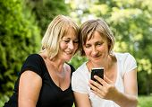 picture of mature adult  - Adult daughter showing on smartphone to her mature senior outside in nature - JPG