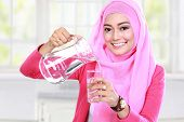 stock photo of muslimah  - portrait of beautiful young muslim woman pouring water into a glass - JPG