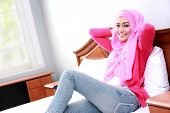 pic of muslimah  - side view portrait of young muslim woman relaxing body on bed - JPG
