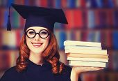 pic of graduation gown  - graduating student girl in an academic gown with books - JPG