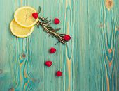 lemon slices, raspberry and rosemary on turquoise colored wooden desk