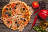 Sliced Italian Pizza Margherita With Tomatoes, Olives And Basil On Rustic Background Top View