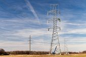 pic of electricity pylon  - High voltage electricity pylon with workers on it building up a new power line on blue sky background with clouds - JPG