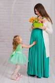 Young pregnant woman in a turquoise dress  and little girl