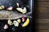 image of bass fish  - Baked Fish with lemon and onion on a tray - JPG