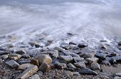 Long Exposure Of Ocean Water Tide On Rocky Pebble Beach