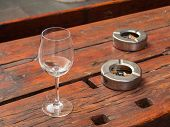 A Glass And Two Ashtrays Outside A Pub