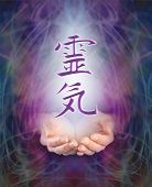picture of healing hands  - Female cupped hands with the Japanese Reiki Symbol floating above on a swirling misty energy purple background - JPG