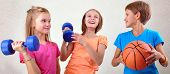 foto of sportive  - Team portrait of sportive kids friends with dumbbells and ball - JPG