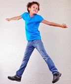 picture of sportive  - Portrait of a cute sportive cheerful happy boy with his hands up jumping and dancing - JPG
