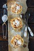pic of pie-in-face  - Mini apple pies from above on wooden background selective focus - JPG